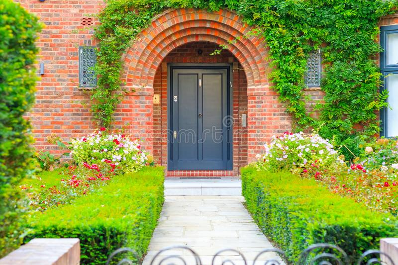 Front door of an English cottage decorated with garden plants and flowers. In Hampstead Heath, London stock photos