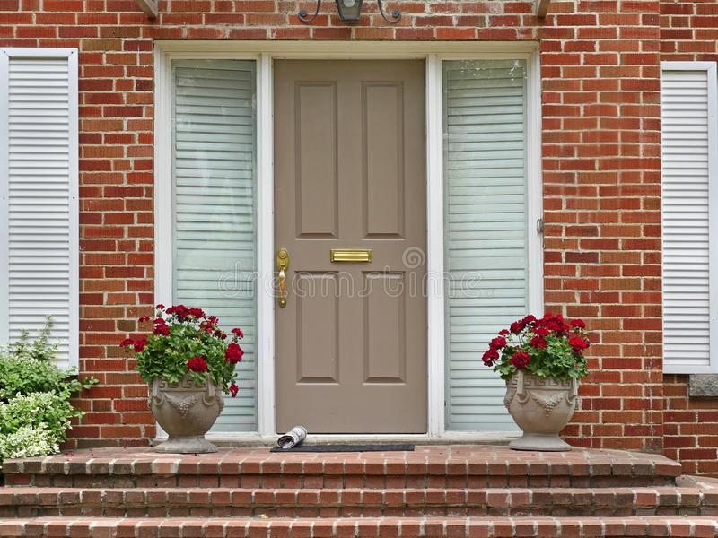 Front door. With newspaper and pots of geraniums stock images
