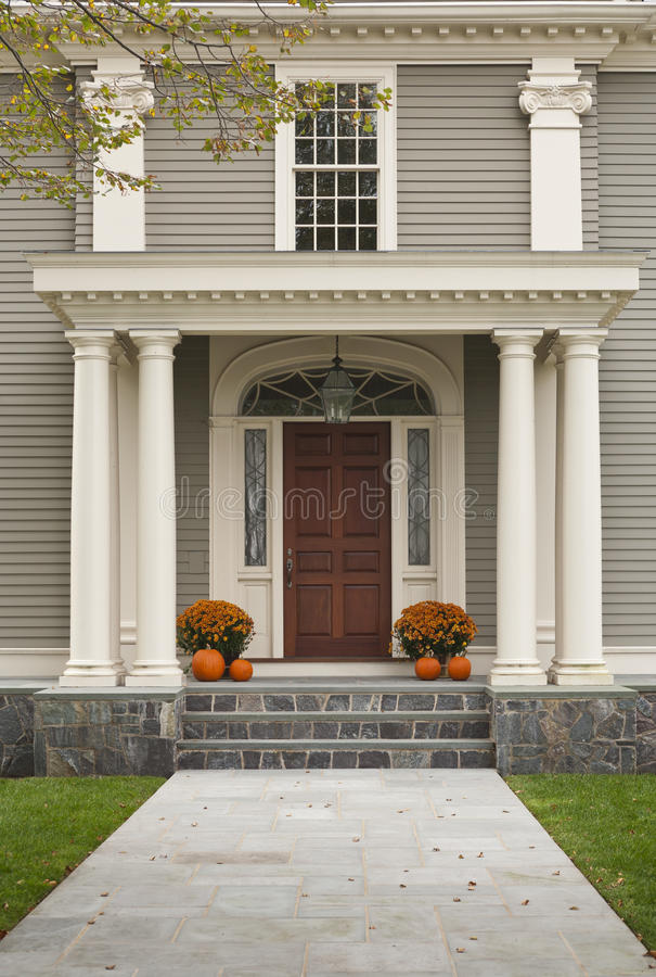Front Door with Front Porch and Pillars. Front Door of Home showing two pillars with arch and twin flowerpots with four pumpkins, 2 on each side. Shows stone stock images