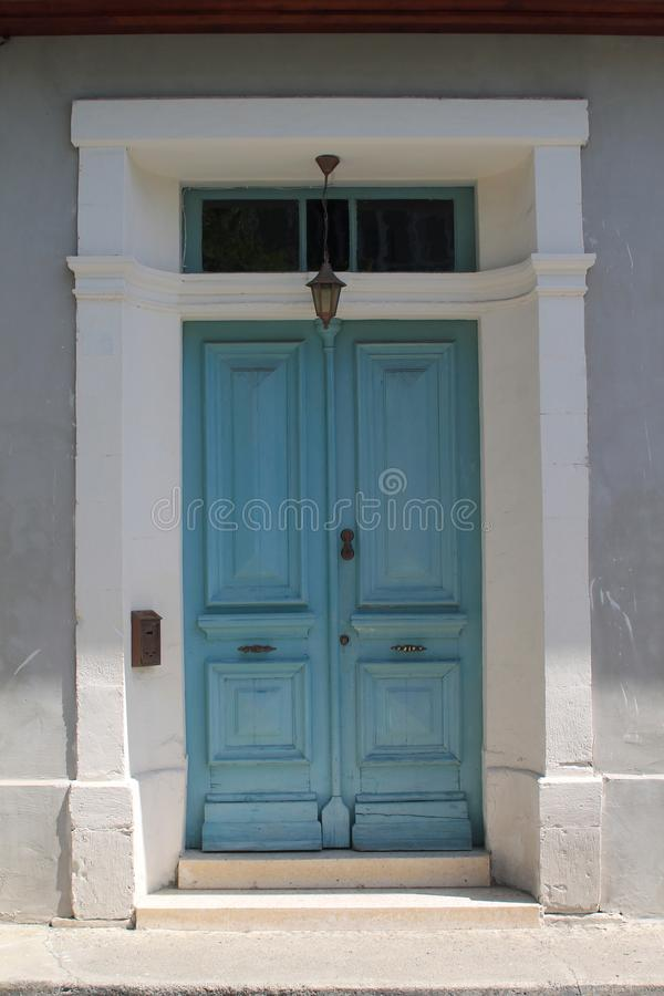 Front door with lantern and mailbox. Old-fashioned blue wooden front door with a lantern and a mailbox in a white stone wall stock photo