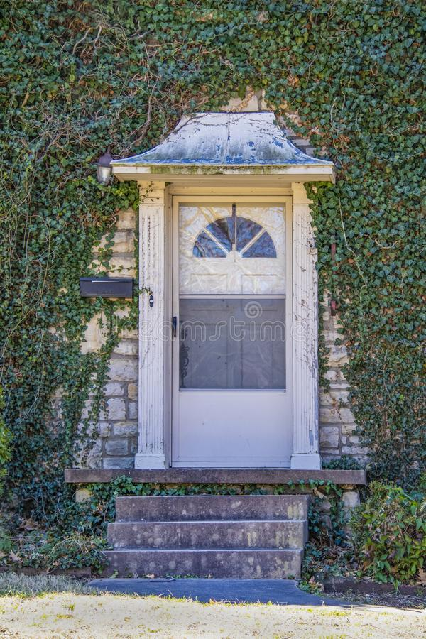 Front door with metal awning - old and worn but beautiful - set in ivy covered rock house - Close-up of entrance stock images