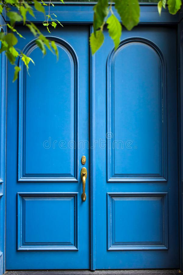 Front doors.Blue paint. Exterior house detail. Blue painted antique-style double doors are closed. Secret is behind. Front doors with natural light. Exterior royalty free stock image