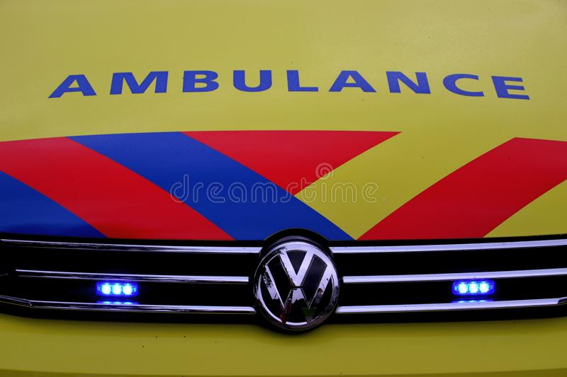 Front of a dutch ambulance in yellow with blue and red striping royalty free stock photo