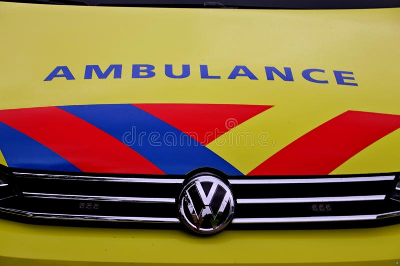 Front of a dutch ambulance in yellow with blue and red striping royalty free stock photography