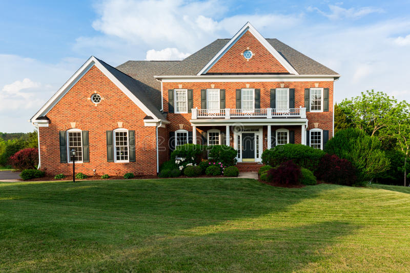 Front elevation large single family home. Front of home and garage of large single family modern US house with landscaped gardens and lawn on a warm sunny royalty free stock image