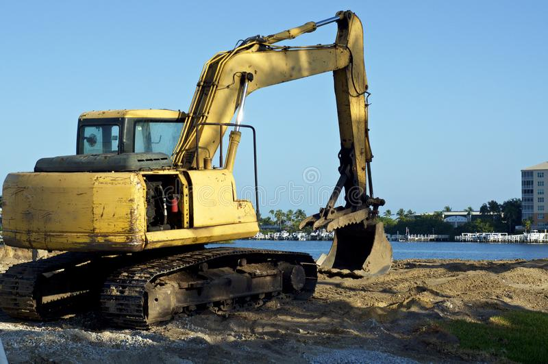 Front end bucket loader at waters edge. A yellow front end bucket loader excavator sits on land at the water`s edge at bay in Bonita Springs Florida on a sunny royalty free stock image