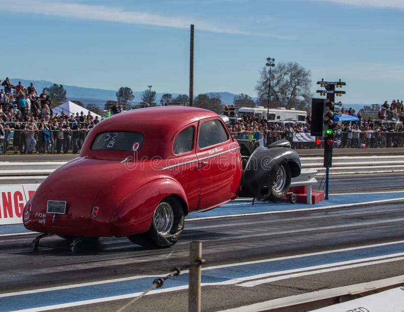 Front End Lift. Redding, California: The front end of a hot rod lifts in the air as the car gets the green light on a start at the drag races stock images