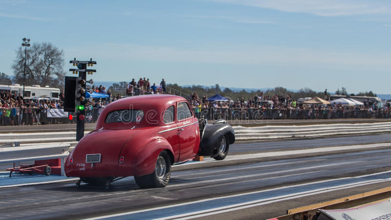 Front End Lift. Redding, California: The front end of a hot rod lifts in the air as the car gets the green light on a start at the drag races royalty free stock photo
