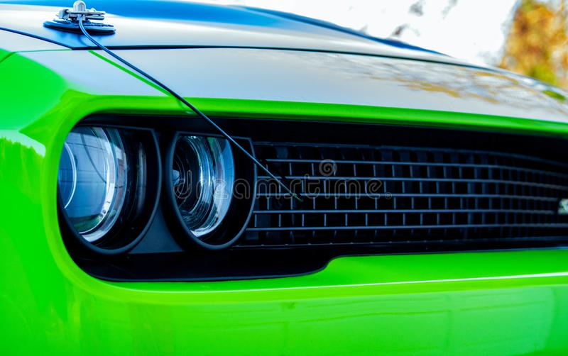 Green Front of Sports Car. Front-end of a lime green sports car. Black grill in front with headlights. Black hood on top royalty free stock photos