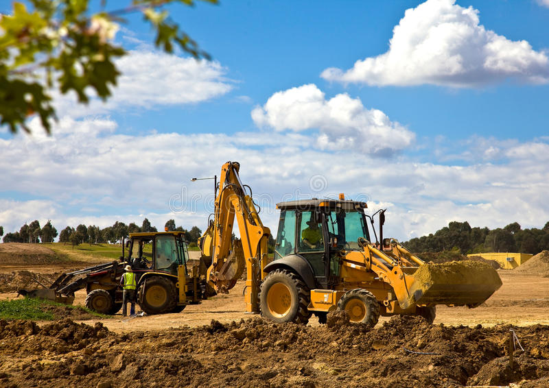 Front end loader with backhoe in action royalty free stock photos