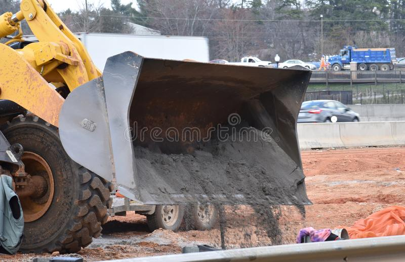 Front end loader dumps a load of gravel. A front end loader dumps a load of gravel on a highway construction site royalty free stock photo