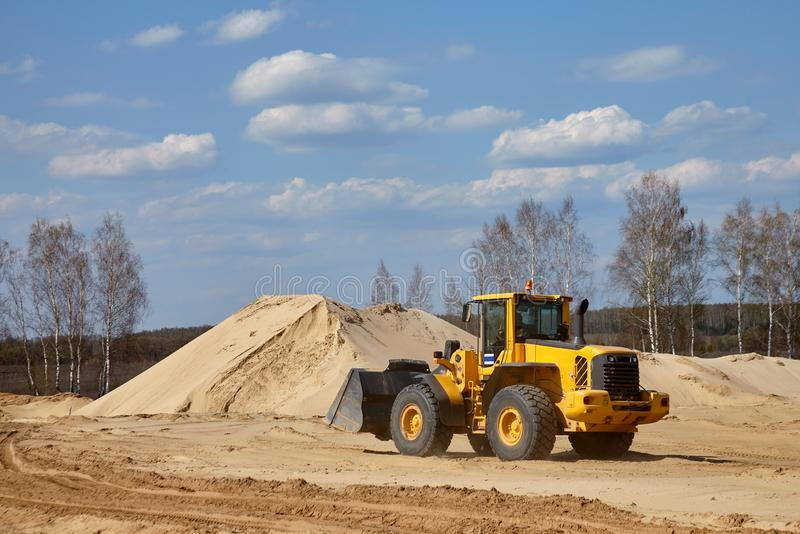 Front end loader scoops up a sand near an aerated concrete plant.  stock photos
