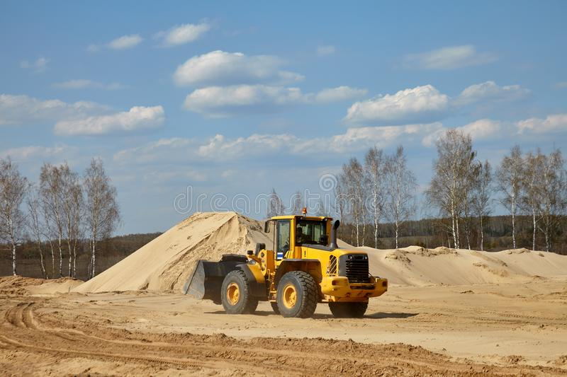 Front end loader scoops up a sand near an aerated concrete plant.  royalty free stock images