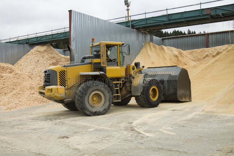 Front End Loader Working in Sawdust Storage Area. Front end loader is loading sawdust to its scoop in storage area stock images