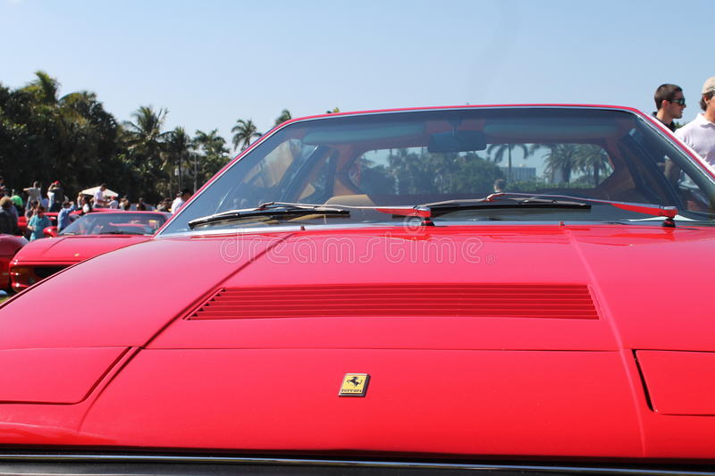 Front end red Ferrari. Front end Ferrari Dino 308 GT4 hood and windshield. lined up among other red Ferrari sports cars and around people. outdoors on a sunny royalty free stock photo