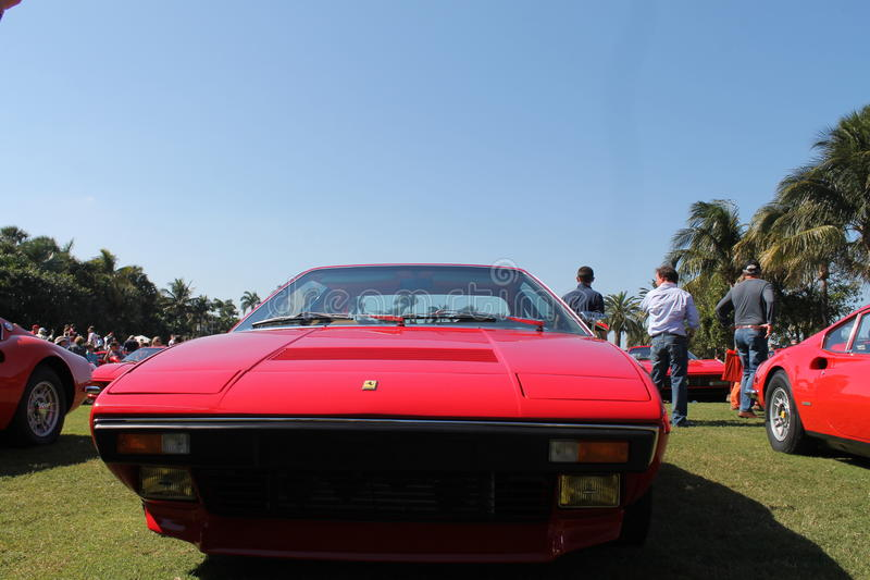 Front end red Ferrari. Front end Ferrari Dino 308 GT4 lined up among other red Ferrari sports cars and around people. outdoors on a sunny day royalty free stock images