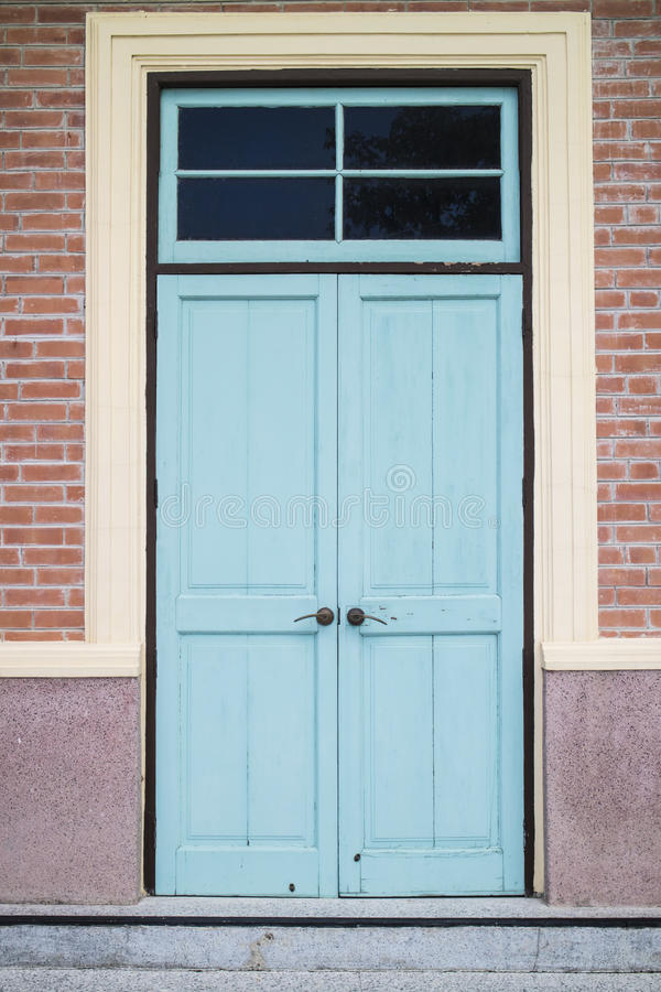 A front entrance of a museum with a blue door and red brick siding stock photography