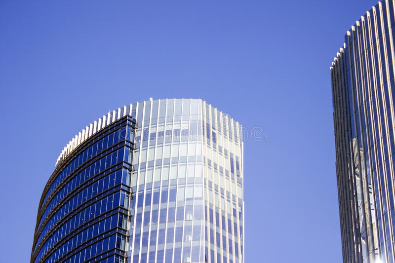Front façade of a blue corporate building next to its twin building. stock images