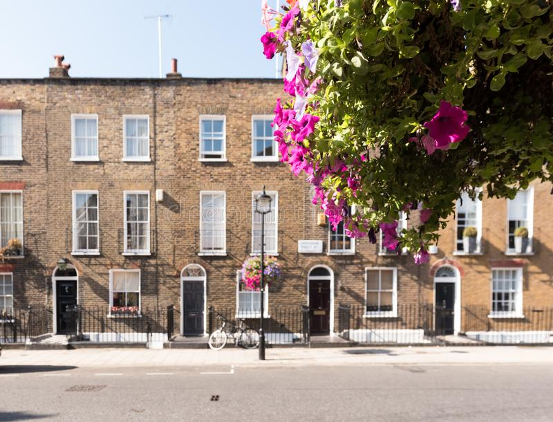 London Terrace Houses. Front facades and arched doors of historic brick London Terrace houses with tall windows and iron railing out front with a bicycle on the stock photography