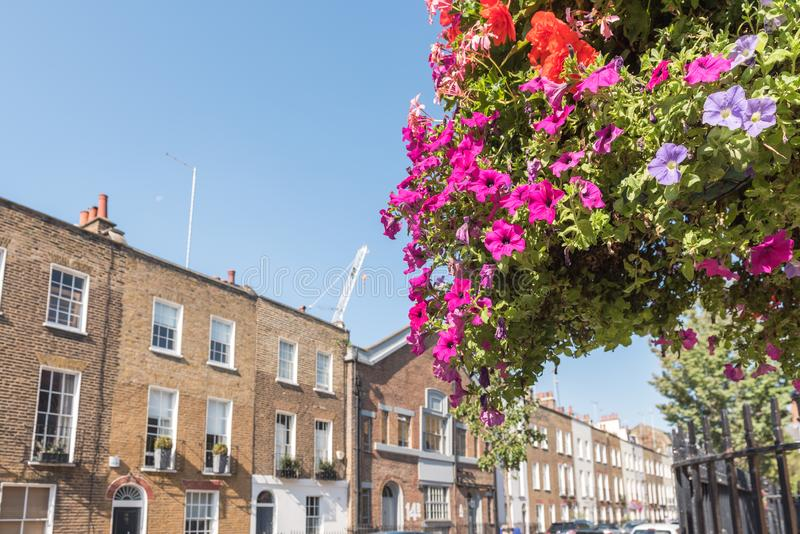 London Terrace Houses. Front facades and arched doors of historic brick London Terrace houses with tall windows and iron railing out front with a bicycle on the royalty free stock photo