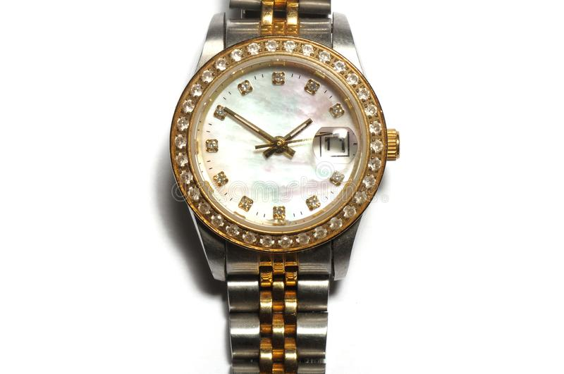 A silver ladies watch with a round watch face and diamonds on the rim. A front facing closeup photo taken on a silver ladies watch with a round watch face and stock photography