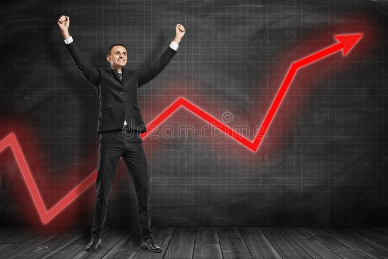 Front full length view of happy businessman raising arms in triumphant gesture with red graph arrow going up behind him royalty free stock photos