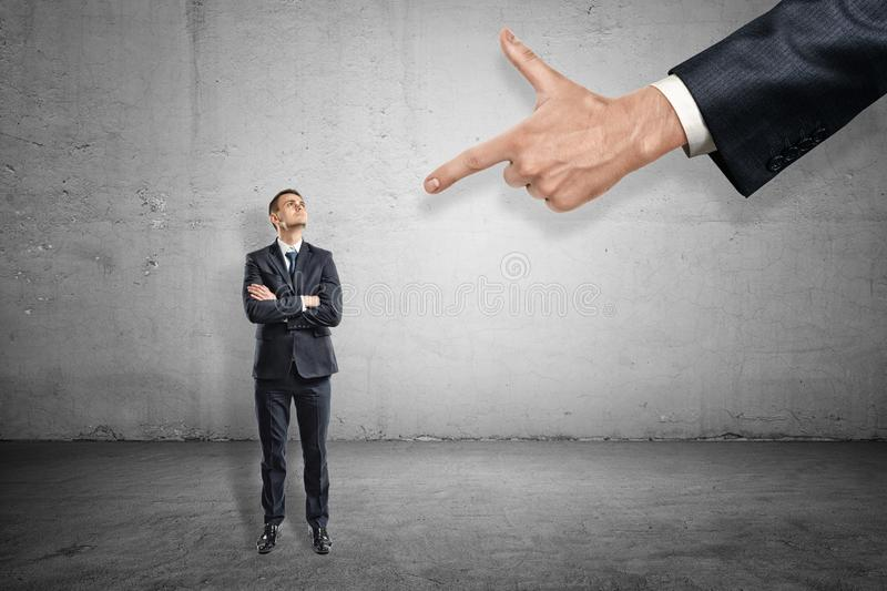 Front full length view of little businessman standing and looking up at huge hand pointing index finger at him. royalty free stock photo