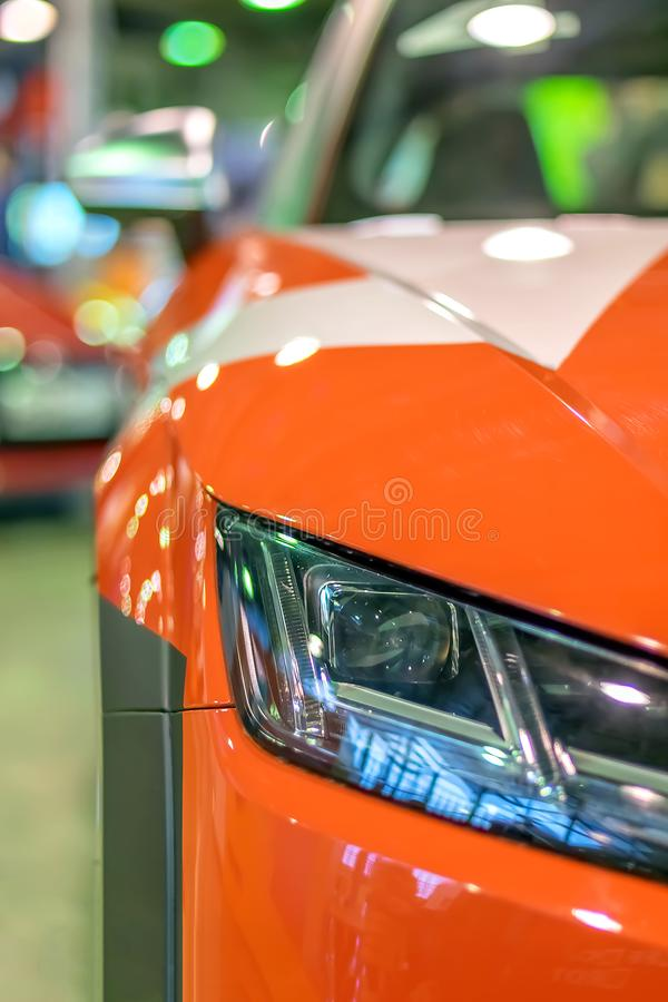 Front headlight of a sports racing red car, on autoexhibition autobody. Red racing sports car shines and shimmers in the lights of the auto show stock images