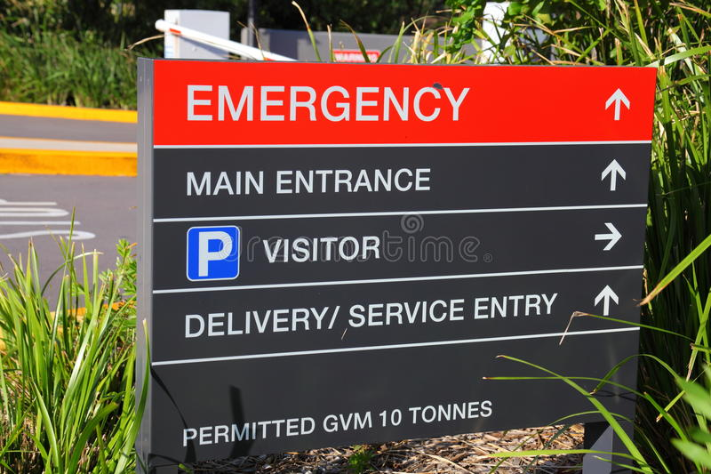 Emergency sign. A sign-board of a hospital showing the way to the emergency entrance, the main entrance, visitor parking, delivery and service entry ( stock image