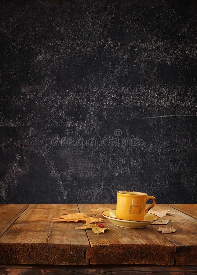 Front image of coffee cup over wooden table and autumn leaves in front and blackboard background with room for text stock image