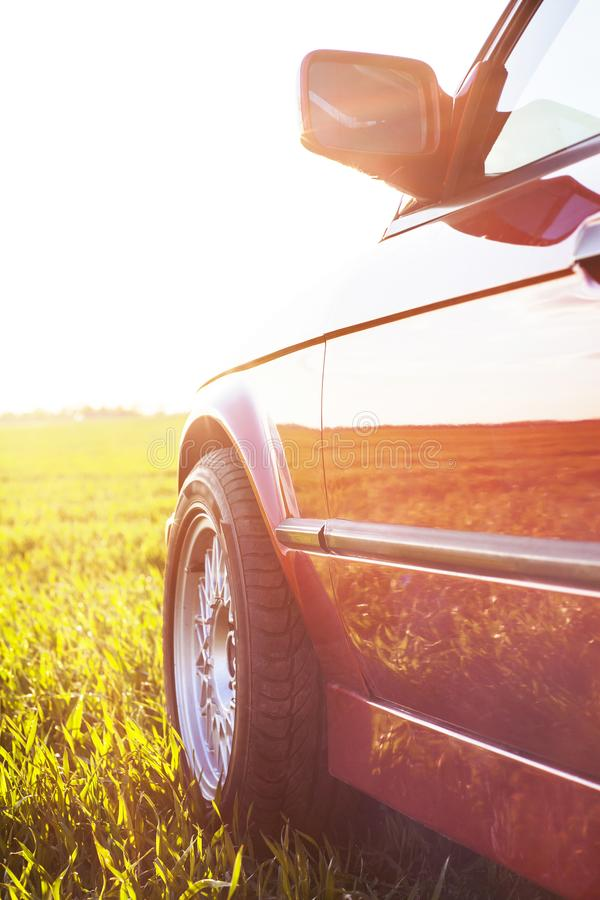 Front left side of an old German car that stands on green grass at sunset stock images