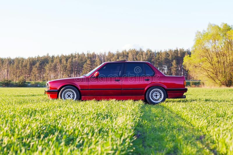 Front left side of an old German car that stands on green grass at sunset stock photography
