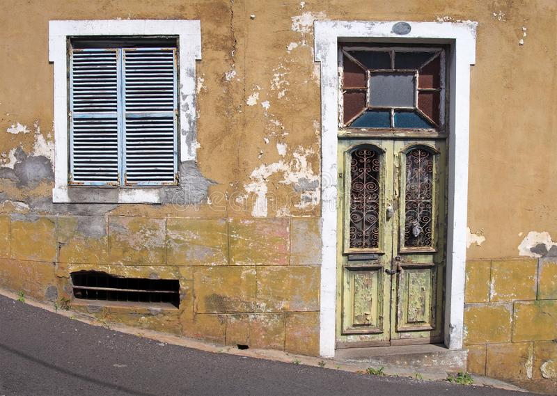 Front of an old abandoned yellow house with blue shuttered windows and locked green wooden door with flaking peeling paint on. The front of an old abandoned stock photos