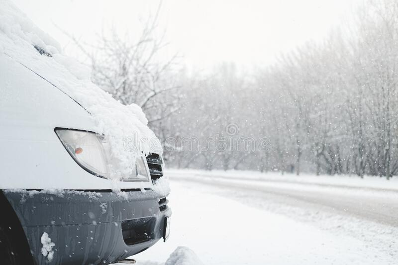 The front part of a car covered in snow. Vehicle stands by the snowy road in stormy weather stock photos