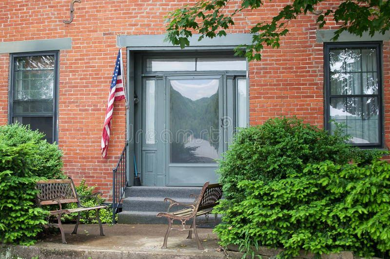 Front Porch. Two rusty benches sit on the concrete porch outside a historic brick Federal style home in the USA. An American flag hangs by a glass door that stock photo