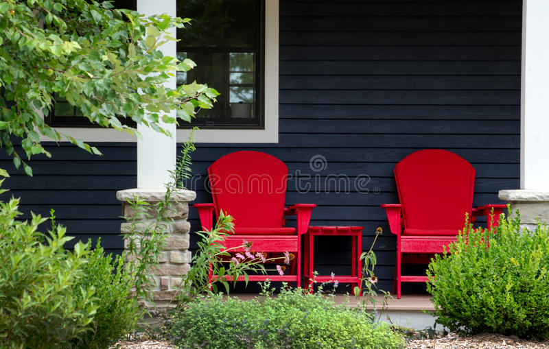 Red chairs on a front porch. Two red adirondack chairs sit on a front porch beach house waiting for someone to sit back and relax royalty free stock photos