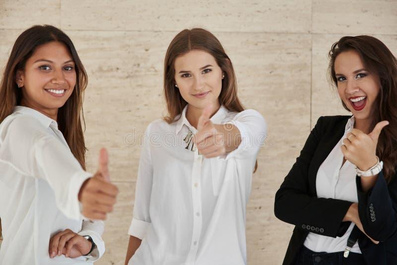 Happy businesswomen showing thumbs up stock image
