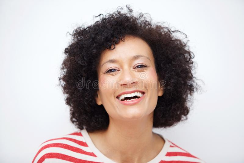 Front portrait of and older african american woman laughing against white background stock images