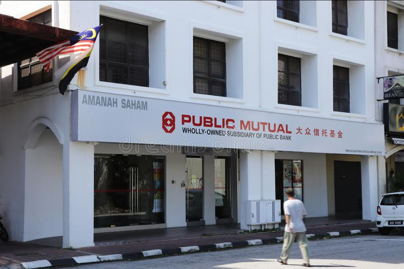 Front Of Public Mutual Fund`s Office, Ipoh Branch. An elderly man walking with motion blur in front of the Public Mutual Fund office, Ipoh Branch royalty free stock image