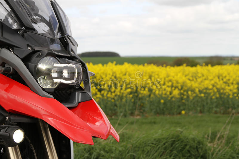 Front of a red BMW R1200GS in a field. A red BMW R1200GS motorcycle showing a field and a cloudy sky. LED headlight and spotlights, screen and red beak royalty free stock image