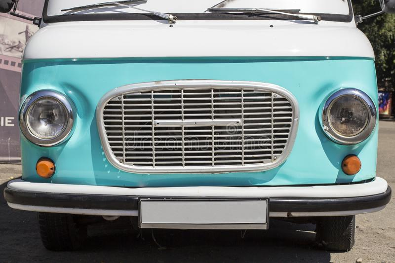Front of a retro car. Turquoise exclusive car. Bumper, grille, headlights. The concept of travel, delivery. Minibus stock image