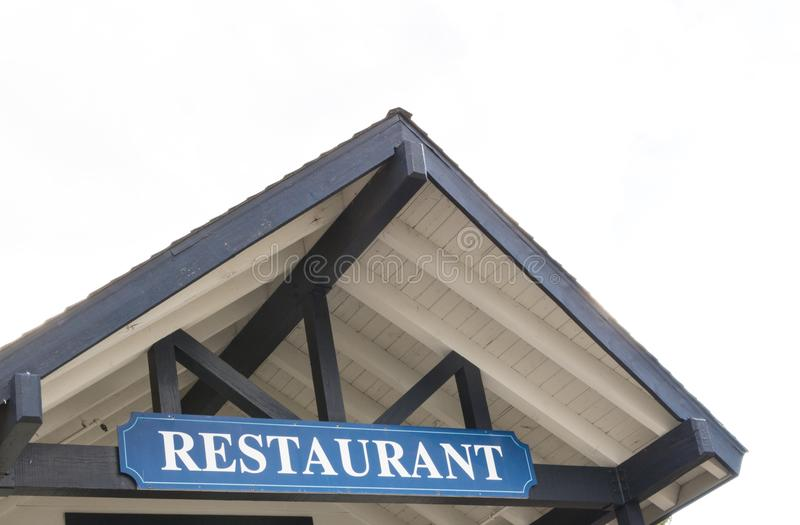 Front of rustic style restaurant, resturant sign. Front of rustic style restaurant, large blue sign white letters reads RESTAURANT, peaked roof, window over stock images