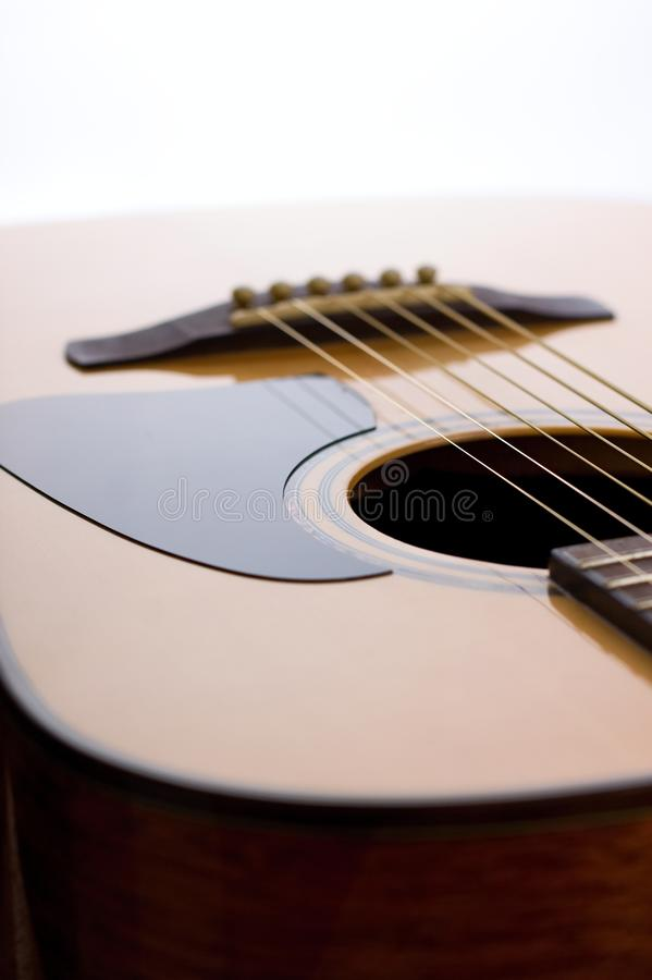 Front side of acoustic guitar with pickguard. Vertical photo of top solid spruce board of acoustic guitar with golden strings and black pickguard in the stock photography