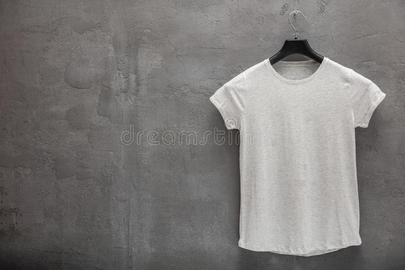 Front side of female grey melange cotton t-shirt on a hanger and a concrete wall in the background royalty free stock photos