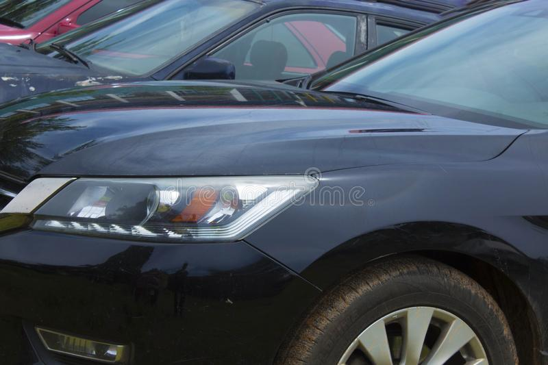 Image of front side of four car showing headlights suitable for commercial illustration of used cars concepts. Front side of four used cars with no logos in royalty free stock images