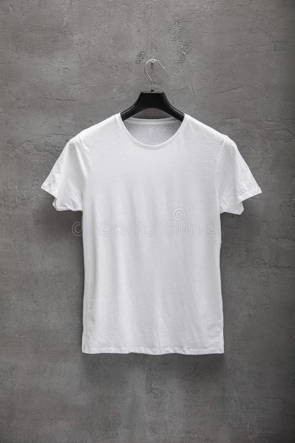 Front side of male white cotton t-shirt on a hanger and a concrete wall in the background. T-shirt without print royalty free stock photo