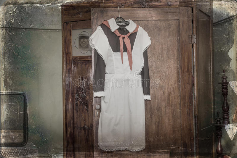 The front Soviet school uniform with a pioneering tie. Hanging on the door of the old cabinet stock image