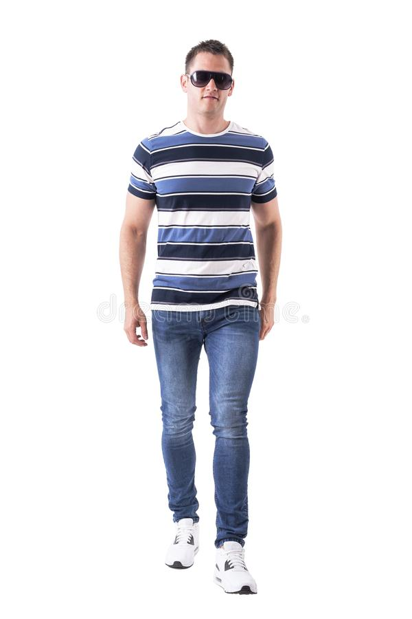 Front view of adult stylish man with sunglasses approaching and looking at camera. Full body isolated on white background royalty free stock photos