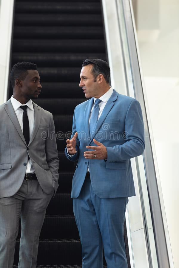 African-american young male executive talking with mature male executive in escalator royalty free stock photos
