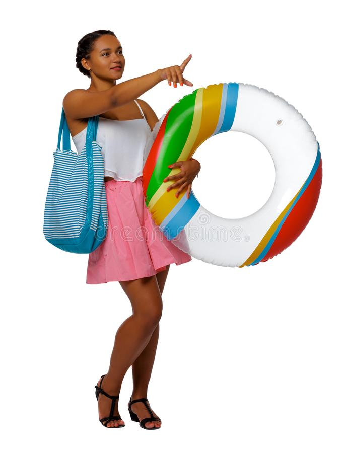 Front view of an afro american woman with an inflatable circle which points hand up royalty free stock photo